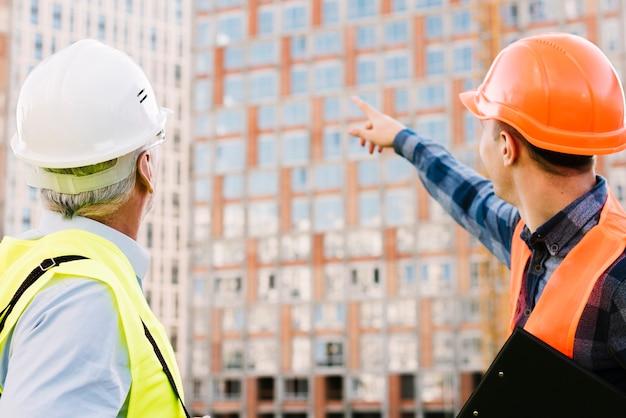 Mannen met helmen en veiligheidsvesten kijken naar gebouw Gratis Foto