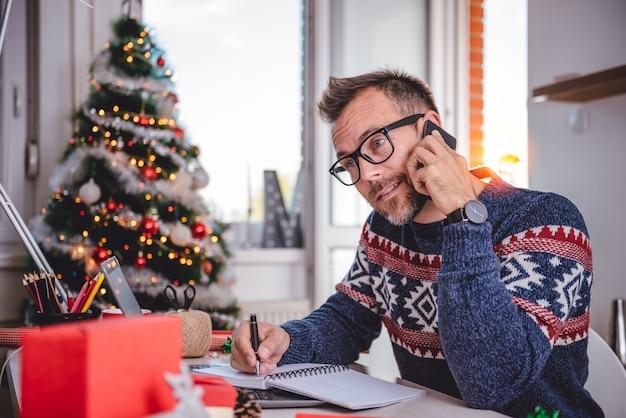Mannen praten op slimme telefoon en notities schrijven Premium Foto