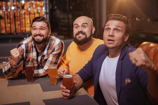 Mannen schreeuwen tijdens het kijken naar voetbalwedstrijd in bier pub Premium Foto