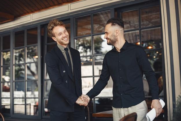 Mannen schudden elkaar de hand. bijlage van een zakelijke overeenkomst. begrip tussen zakenpartners. Gratis Foto