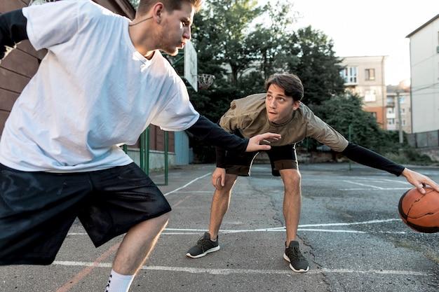 Mannen spelen basketbal op stedelijk hof Gratis Foto