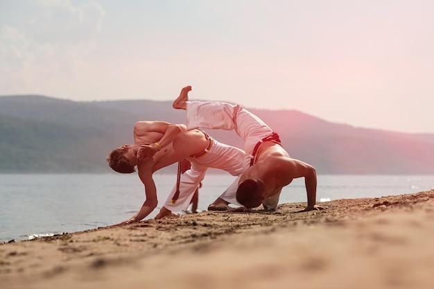 Mannen trainen capoeira op het strand Premium Foto