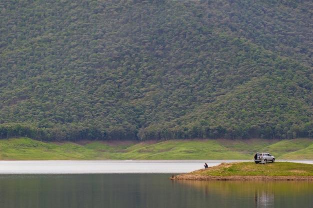 Mannen zitten en vissen op het eiland bij de dam tussen de bergen. Premium Foto