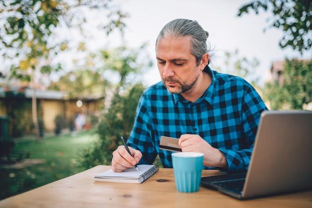 Mannen zitten op het terras in de achtertuin en notities op te schrijven Premium Foto