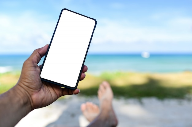 Mannenhand die een witte scherm lege telefoon houden. hij sliep op het strand. Premium Foto