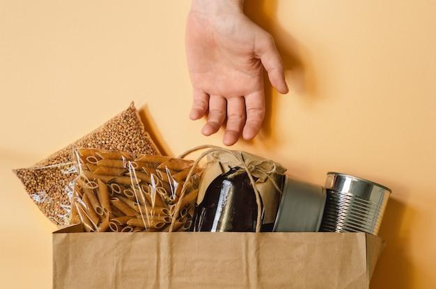 Mannenhand en papieren zak met voedselvoorziening crisis voor quarantaine Premium Foto