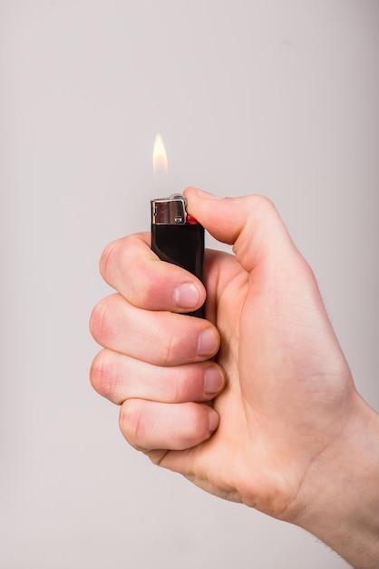 Mannenhand houdt een aansteker vast Premium Foto