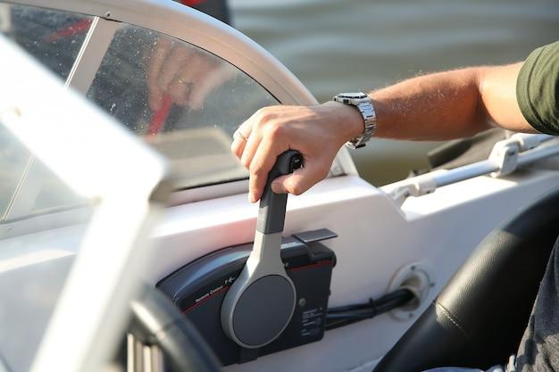 Mannenhand is op de bedieningshendel van een witte motorboot close-up Premium Foto