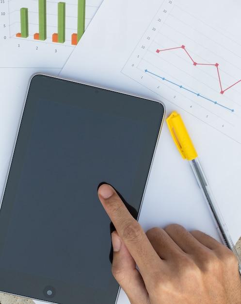 Mannenhand met grafiek van bedrijfsdocument met digitale tablet Premium Foto