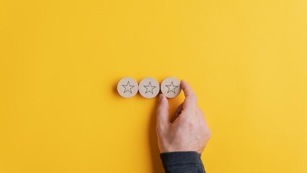 Mannenhand plaatsen van drie houten gesneden cirkels met stervorm op hen in een rij op gele achtergrond. Premium Foto