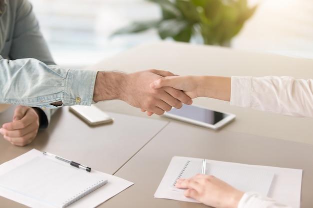 Mannenhand schudden hand van jonge vrouw over bureau Gratis Foto