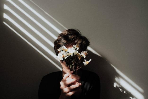 Mannetje dat een klein boeket bloemen voor zijn gezicht houdt met lichte lijnen die op hem glanzen Gratis Foto