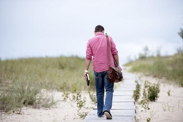 Mannetje dat een notitieboekje houdt lopend op een houten weg in het midden van zandige oppervlakte Gratis Foto