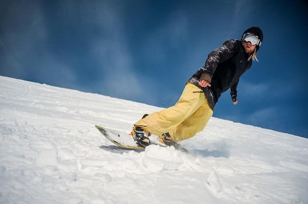 Mannetje dat snowboarder onderaan de berghelling berijdt Premium Foto