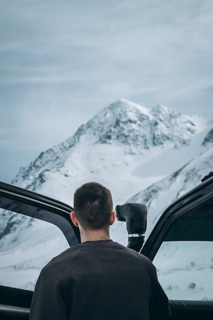 Mannetje dat zich naast zijn 4x4 auto bevindt en mooie sneeuwbergen in de alpen bekijkt Gratis Foto