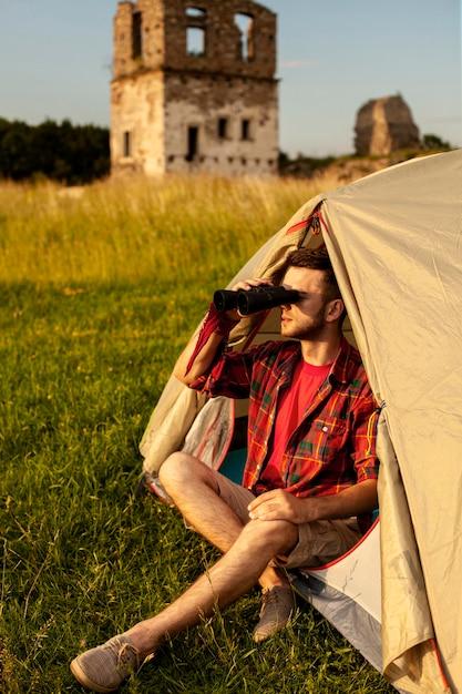 Mannetje die in het kamperen tent binoculair kijken Gratis Foto