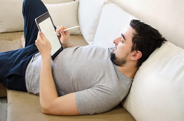 Mannetje die naald op te trekken tablet gebruiken Premium Foto