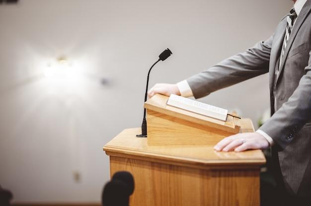Mannetje in een formele outfit die de bijbel predikt vanaf de tribune bij het altaar van de kerk Gratis Foto