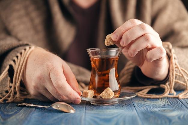 Mannetje voegt suiker toe in hete thee Premium Foto