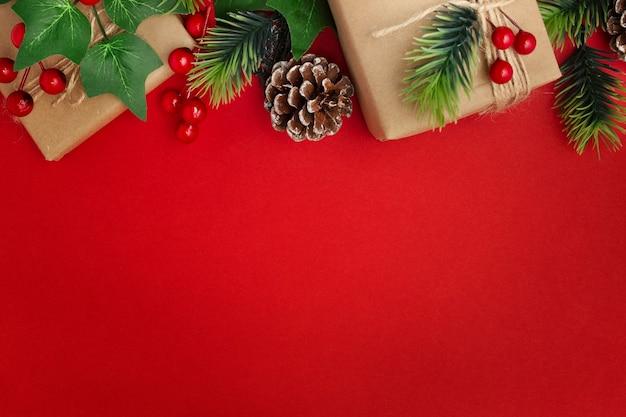 Maretak, dennenappels en kerstcadeaus op rode tafel Gratis Foto
