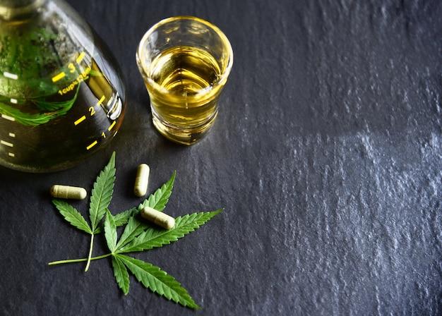 Marihuanablad plant cannabis kruidenthee en capsule op donkere achtergrond Premium Foto
