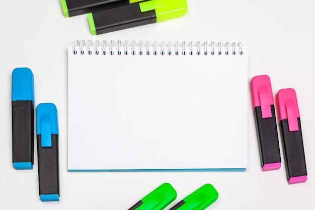 Markeerstiften en blanco kladblok-papier lagen plat op een bureau Premium Foto