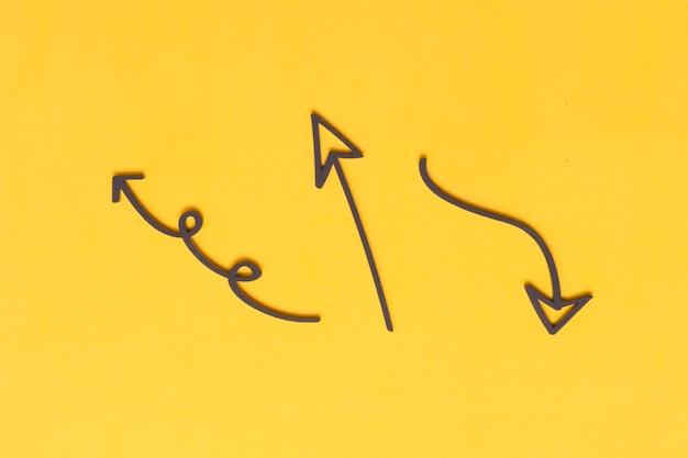Marker pijltekeningen op gele achtergrond Gratis Foto