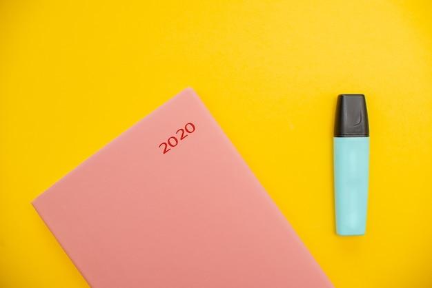 Markering en blocnote op een gele abstracte achtergrond met exemplaar ruimte, minimale stijl. Premium Foto
