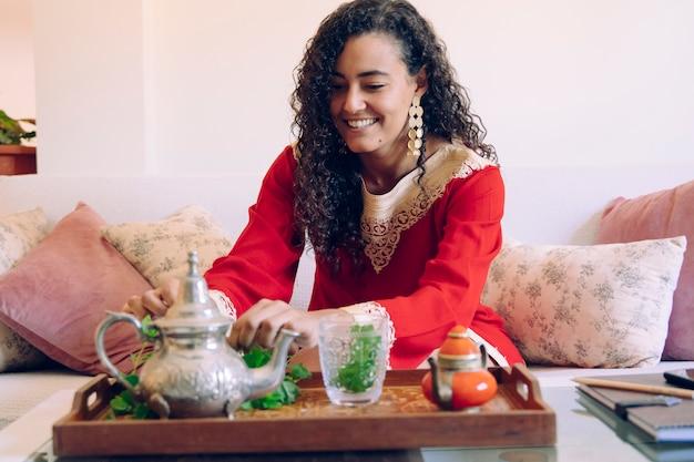 Marokkaans wijfje dat traditionele arabische thee thuis voorbereidt. arabische cultuur en tradities. moslim levensstijl thuis. arabische jonge vrouw met etnische kenmerken die een tak van verse groene munt ruiken. Premium Foto