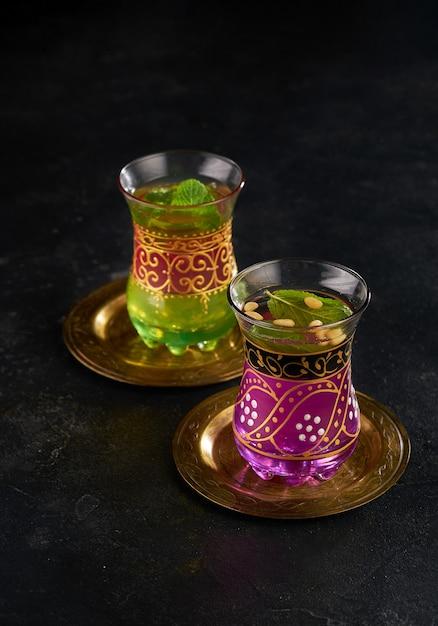 Marokkaanse muntthee in de traditionele glazen op zwarte achtergrond Premium Foto