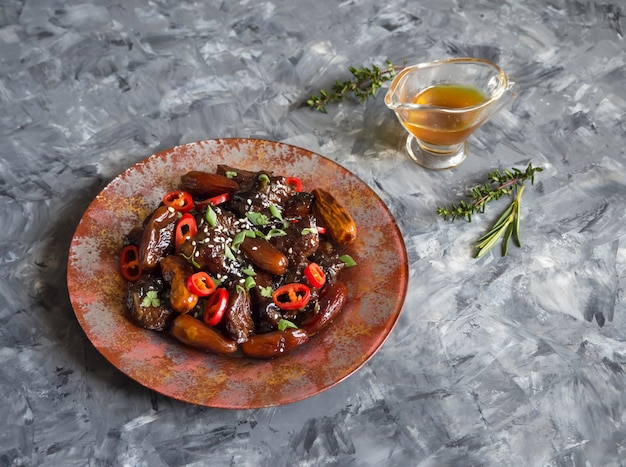 Marokkaanse rundvleestagine met datasaus. knapperig rundvlees in zoete en plakkerige saus. Premium Foto
