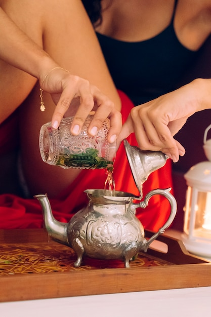Marokkaanse vrouw die traditionele arabische thee thuis voorbereidt Premium Foto