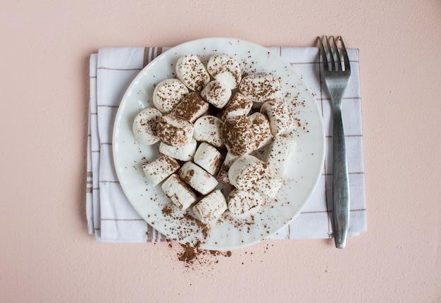 Marshmallows bestrooid met cacao op witte plaat met vork op handdoek. zoet voedsel bovenaanzicht Gratis Foto