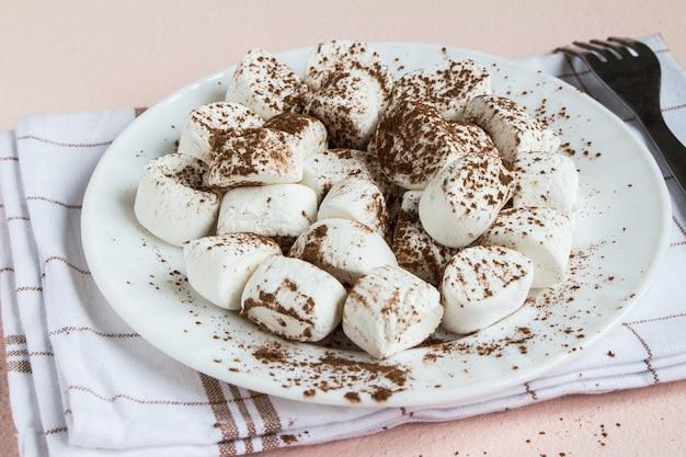 Marshmallows bestrooid met cacao op witte plaat Gratis Foto