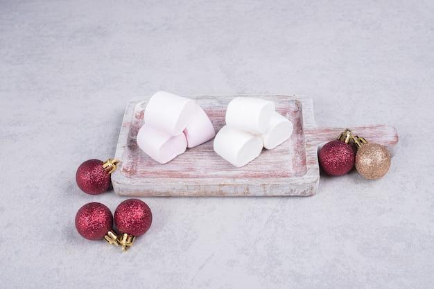 Marshmallows op een houten bord met kerstballen. hoge kwaliteit foto Gratis Foto