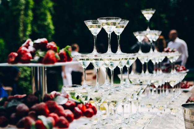 Martini glazen piramide. glazen voor sterke drank op tafel. buffettafel bedekt met een wit tafelkleed. Premium Foto