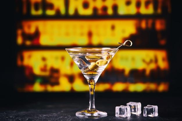 Martini met groene olijven op een tafel in de bar Premium Foto