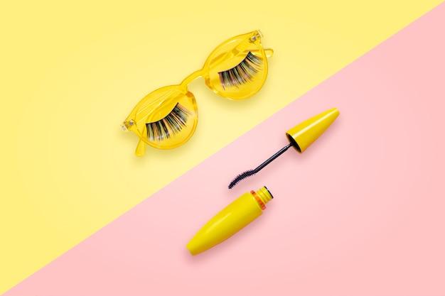 Mascara in gele buis met open penseel op roze en gele zonnebril met nepwimpers. Premium Foto