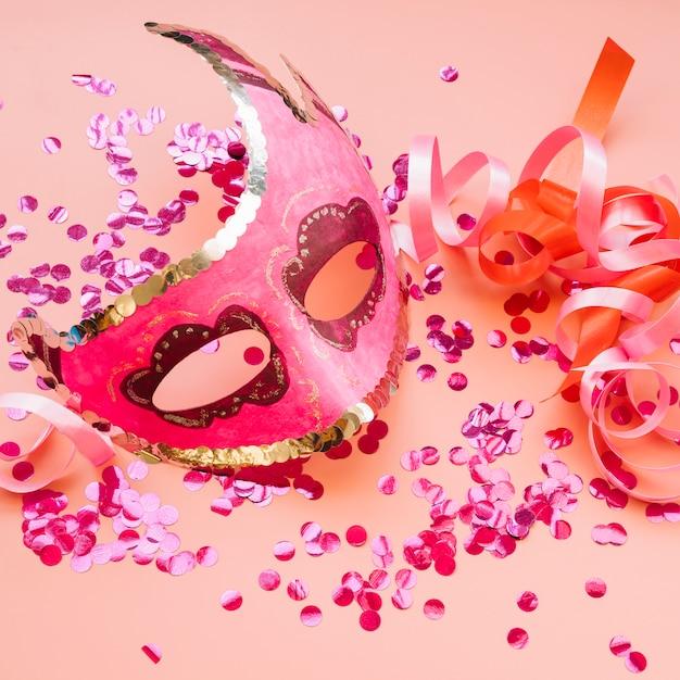 Masker dichtbij linten en reeks roze confettien Gratis Foto
