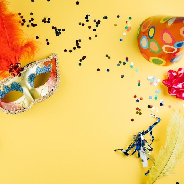 Masker van carnaval van de maskerade met het materiaal van de partijdecoratie en partijhoed over gele achtergrond Gratis Foto