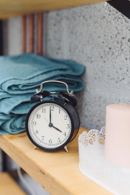 Massagetijd analoge zwarte klok op een plank met blauwe handdoeken en kaarsen. het concept van massageartikelen Premium Foto