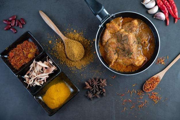 Massaman curry in een koekenpan met kruiden op de cementvloer Gratis Foto