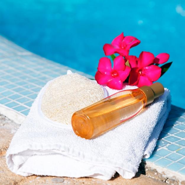 Masseer olie op een witte handdoek naast een zwembad Gratis Foto