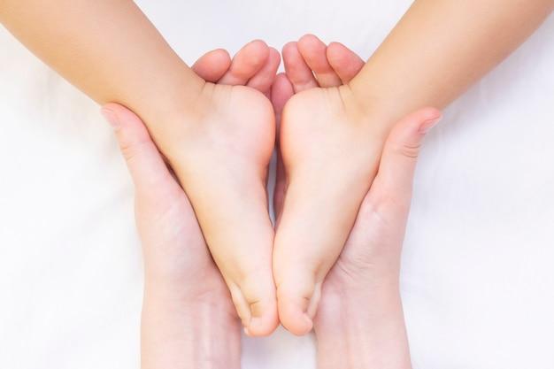 Masseur die een kleine kindervoet masseert. moeder doet massage op haar babyvoet. preventie van platte voeten, ontwikkeling, spierspanning Premium Foto