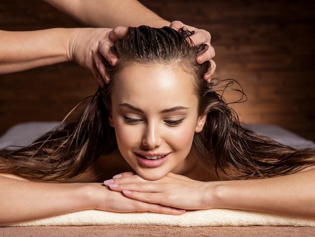 Masseur die het hoofd en het haar voor een vrouw in kuuroordsalon masseert Gratis Foto