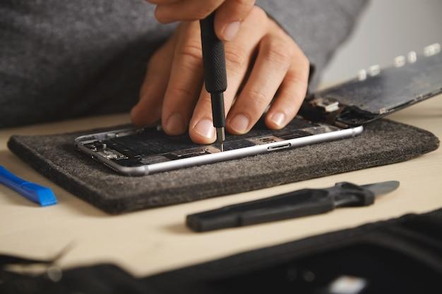 Master gebruikt stuurprogramma om schroeven in elektronische platen van smartphones los te draaien om het te repareren, close-up Gratis Foto