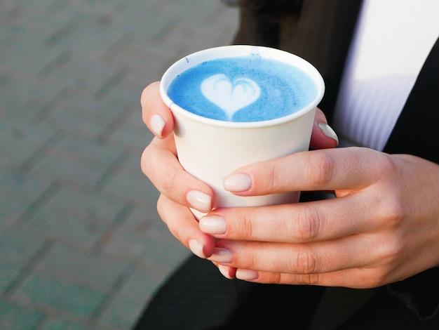 Matcha blauwe thee in de handen. matcha blauwe thee. zijaanzicht van matcha blauwe thee. drink ter plaatse. met een hartvormig patroon. liefde voor de wedstrijd. latte matcha. blauwe latte art Premium Foto