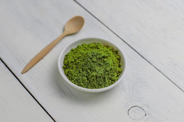 Matcha van word die van gepoederde matcha groene thee en bamboelepel op wit wordt gemaakt. kopiëren Gratis Foto