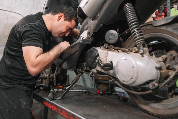 Mechanic repareren scooter motor in reparatiegarage. Premium Foto