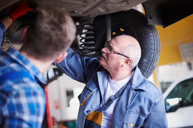 Mechanica die een auto in de werkplaats herstelt Gratis Foto